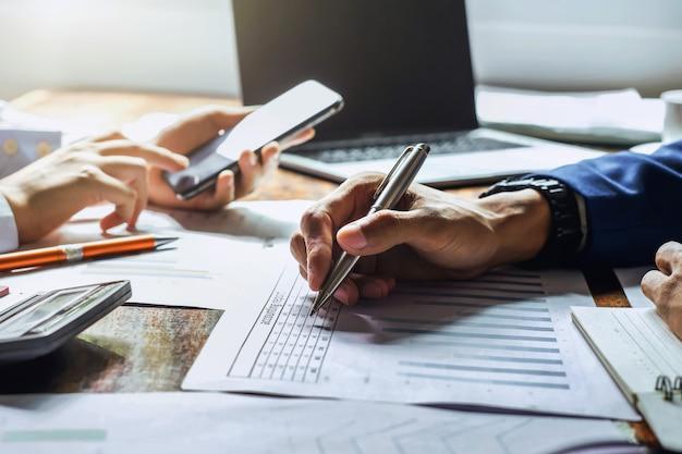Uomo d'affari che lavora in ufficio con l'utilizzo di una calcolatrice per calcolare i numeri concetto di contabilità finanziaria