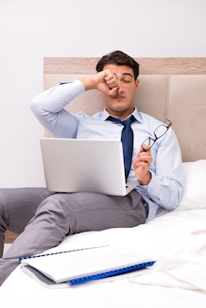 Uomo d'affari che lavora nel letto a casa