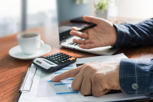Uomo d'affari che lavora nel luogo di lavoro moderno con il computer portatile sulla tavola di legno