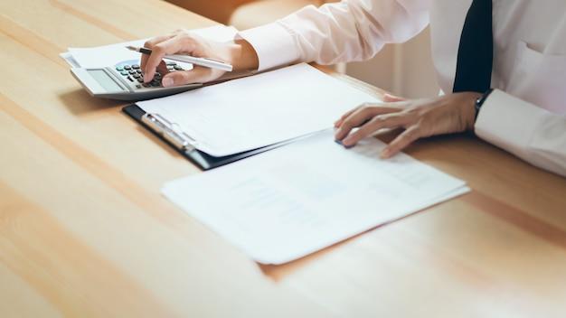 Uomo d'affari che lavora nel suo ufficio con documenti e controllare l'accuratezza delle informazioni.