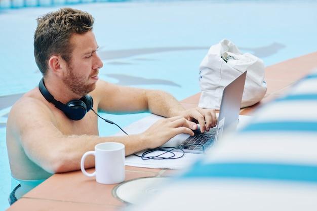 Uomo d'affari che lavora proprio dalla piscina