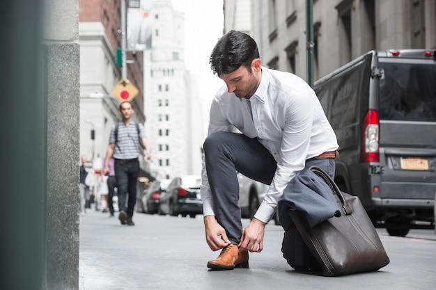 Uomo d'affari che lega i pizzi vicino alla strada