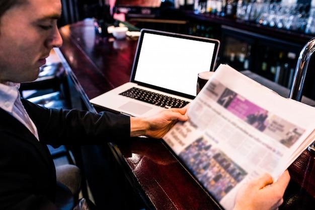 Uomo d'affari che legge le notizie e che utilizza computer portatile al contatore in una barra