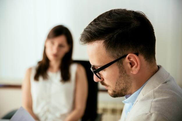 Uomo d'affari che legge un riassunto in un colloquio di lavoro