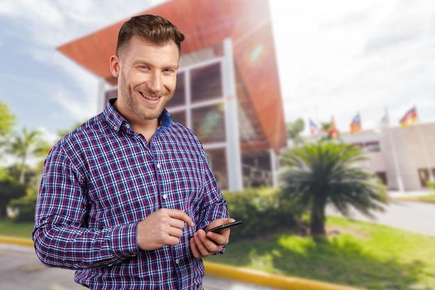 Uomo d'affari che manda un sms sul suo telefono cellulare