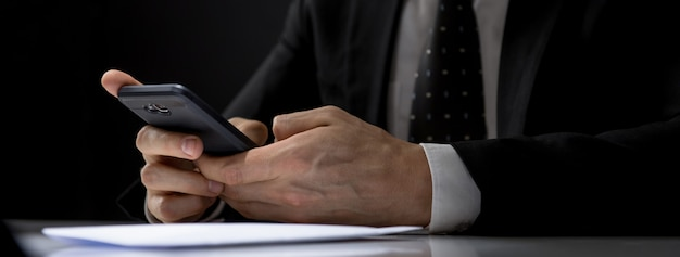 Uomo d'affari che manda un sms sul telefono cellulare al tavolo nella stanza scura