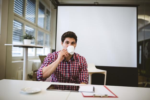 Uomo d'affari che mangia caffè nella sala riunioni