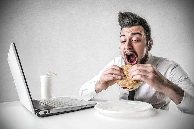 Uomo d'affari che mangia hamburger