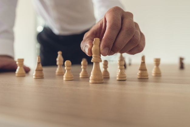 Uomo d'affari che mette avanti la figura di scacchi di re
