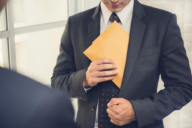 Uomo d'affari che mette la busta nella tasca del vestito