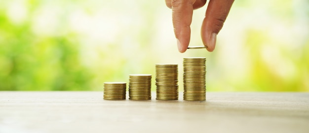 Uomo d'affari che mette la pila dei soldi sulla finanza e sulla contabilità di risparmio di concetto della tavola