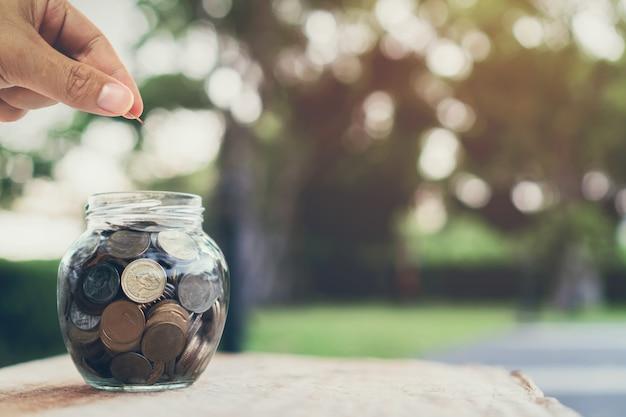 Uomo d'affari che mette le monete sulla bottiglia, sul concetto crescente dei soldi e sul successo di scopo.