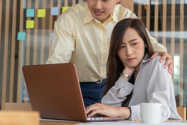 Uomo d'affari che mette mano sulla spalla dell'impiegato femminile nell'ufficio sul lavoro.