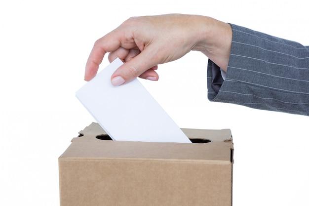 Uomo d'affari che mette scheda elettorale in casella di voto