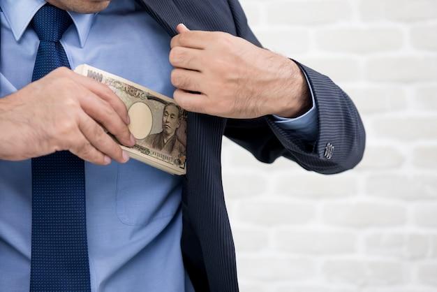 Uomo d'affari che mette soldi, banconote in yen giapponesi, nella tasca del vestito