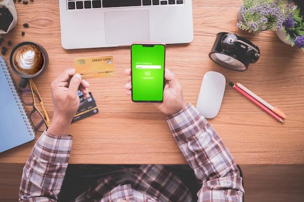 Uomo d'affari che mostra derisione sulla carta di credito e sul telefono cellulare, concetto di acquisto online.