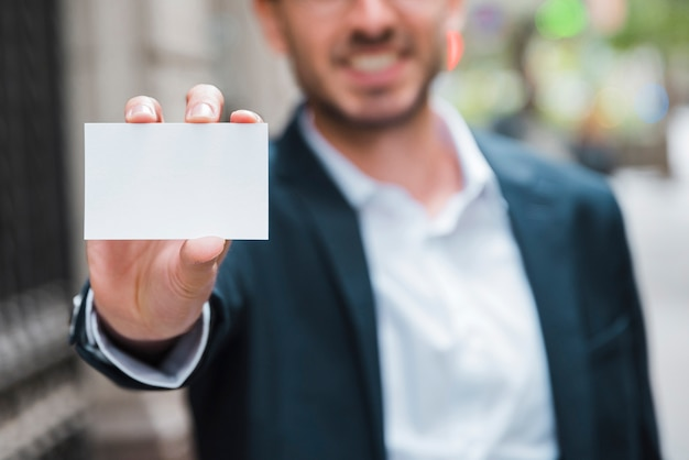 Uomo d'affari che mostra il biglietto da visita bianco verso la macchina fotografica