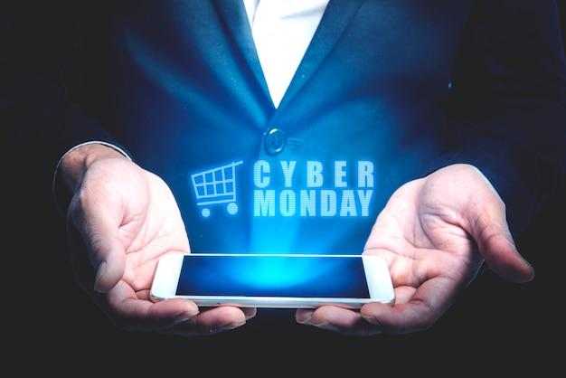 Uomo d'affari che mostra l'annuncio di lunedì di cyber dallo schermo del telefono