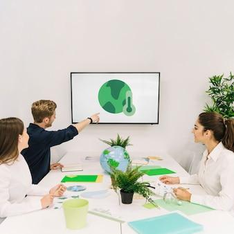 Uomo d'affari che mostra l'icona di riscaldamento globale ai suoi colleghi sullo schermo