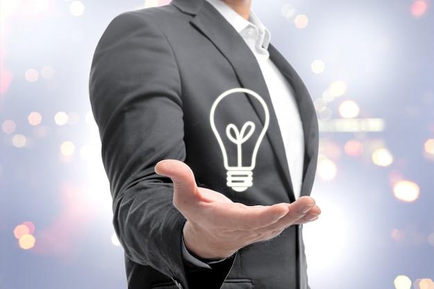 Uomo d'affari che mostra lampadina luminosa nelle mani come simbolo dell'idea innovativa