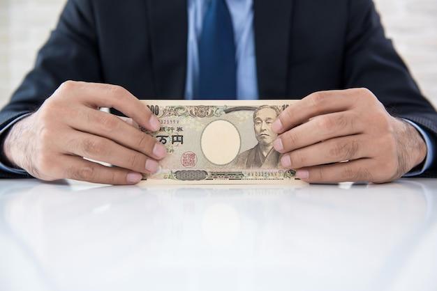 Uomo d'affari che mostra le banconote dei soldi di yen giapponesi sulla tavola