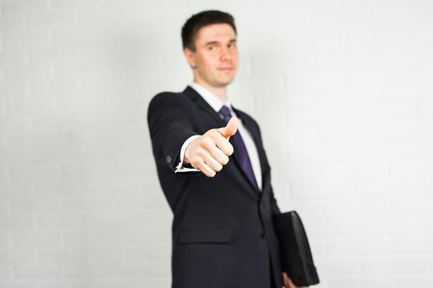 Uomo d'affari che mostra segno giusto con il suo pollice in su.