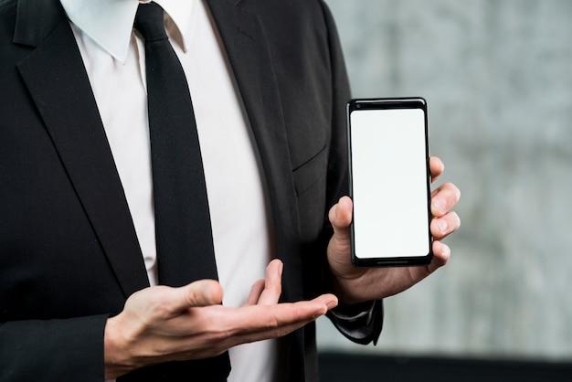 Uomo d'affari che mostra smartphone con lo schermo vuoto