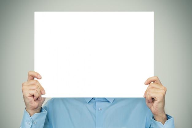Uomo d'affari che mostra sul foglio bianco bianco