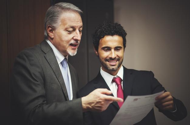 Uomo d'affari che mostra un documento al suo collega