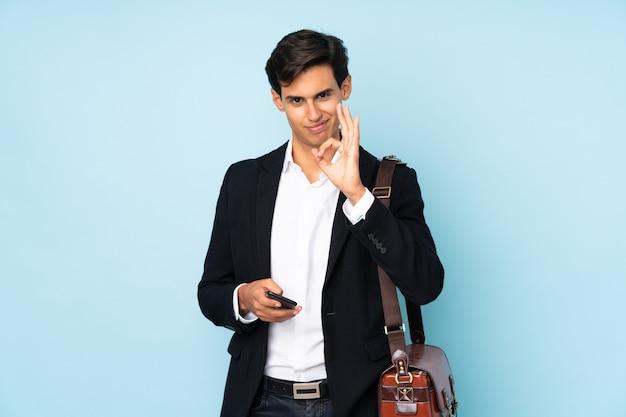 Uomo d'affari che mostra un segno giusto con le dita