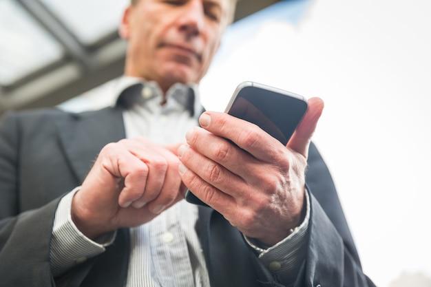 Uomo d'affari che osserva e che scrive sul suo smart phone