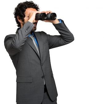 Uomo d'affari che osserva tramite il binocolo
