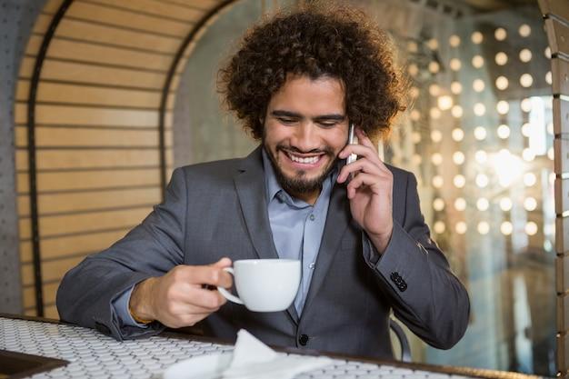 Uomo d'affari che parla sul telefono cellulare mentre mangiando tazza di tè