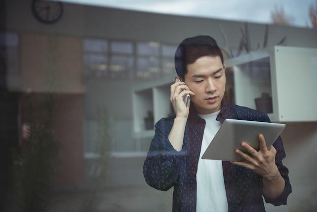 Uomo d'affari che parla sul telefono cellulare mentre per mezzo della compressa digitale
