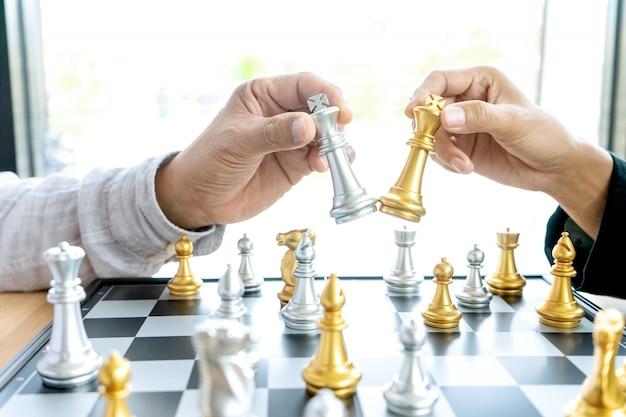 Uomo d'affari che pensa e tiene in mano il re degli scacchi,