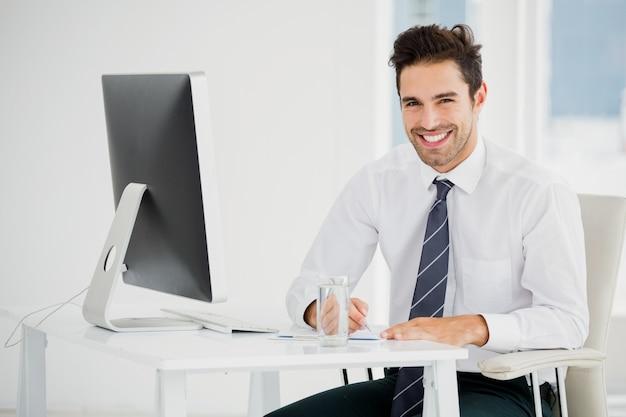 Uomo d'affari che per mezzo del computer e prendendo le note
