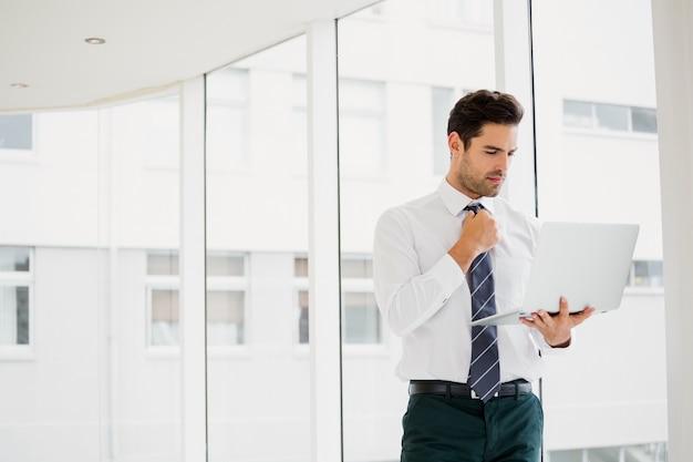 Uomo d'affari che per mezzo del computer portatile e prendendo le note