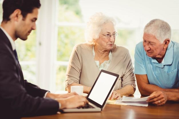 Uomo d'affari che per mezzo del computer portatile mentre la coppia senior sta leggendo i documenti a casa