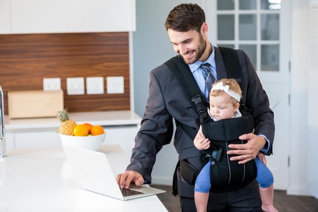 Uomo d'affari che per mezzo del computer portatile mentre portando neonata