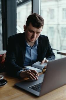 Uomo d'affari che per mezzo del computer portatile mentre sedendosi alla tavola di legno