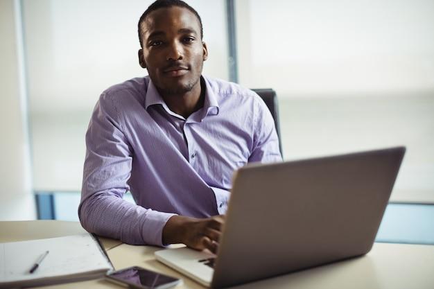 Uomo d'affari che per mezzo del computer portatile