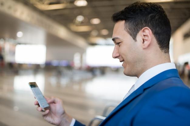 Uomo d'affari che per mezzo del suo telefono cellulare