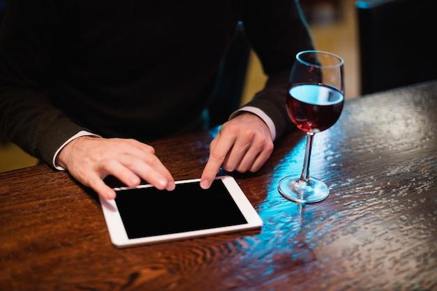 Uomo d'affari che per mezzo della compressa digitale con il vetro di vino sul contatore