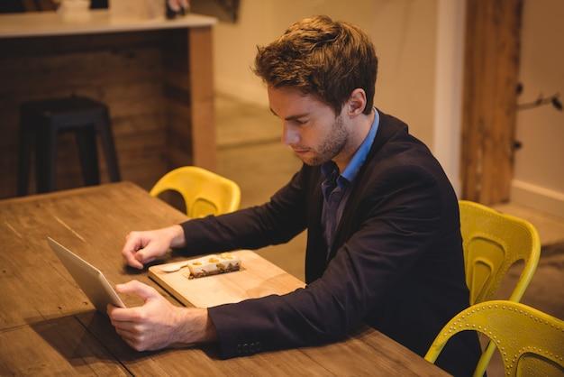 Uomo d'affari che per mezzo della compressa digitale mentre mangiando gli spuntini