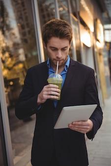 Uomo d'affari che per mezzo della compressa digitale mentre mangiando succo