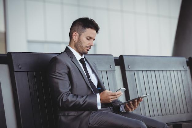 Uomo d'affari che per mezzo della compressa e del telefono cellulare digitali