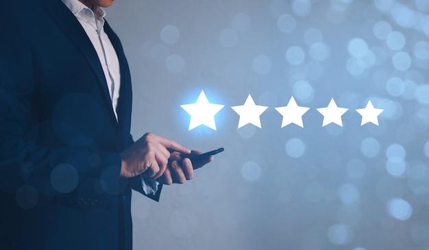 Uomo d'affari che per mezzo dello smart phone con il simbolo della stella dell'icona per aumentare la valutazione della società. concetto di esperienza del servizio clienti.