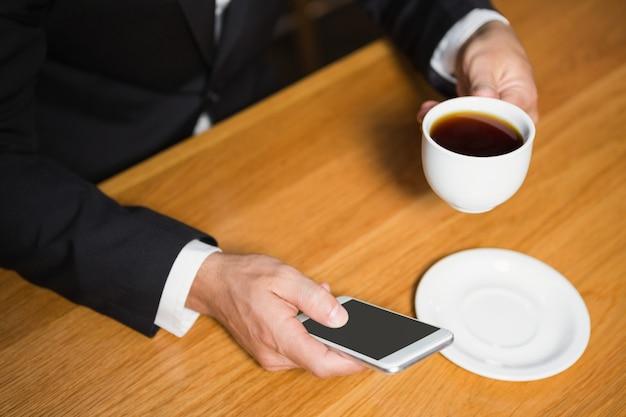 Uomo d'affari che per mezzo dello smartphone e mangiando caffè