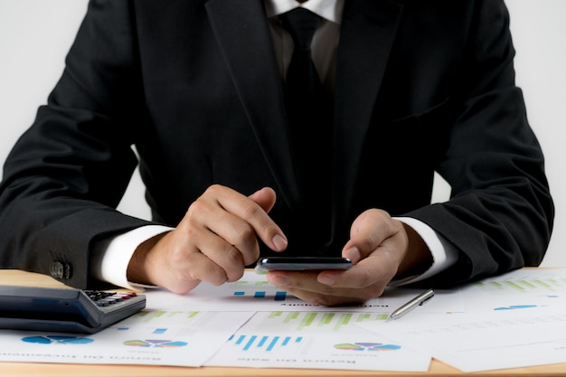 Uomo d'affari che per mezzo dello smartphone sopra lo scrittorio con carta per documenti all'ufficio.
