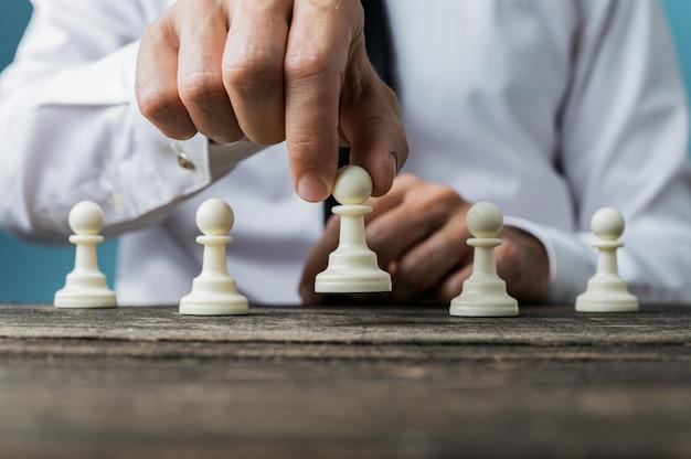 Uomo d'affari che posiziona il pezzo degli scacchi bianco del pegno davanti agli altri